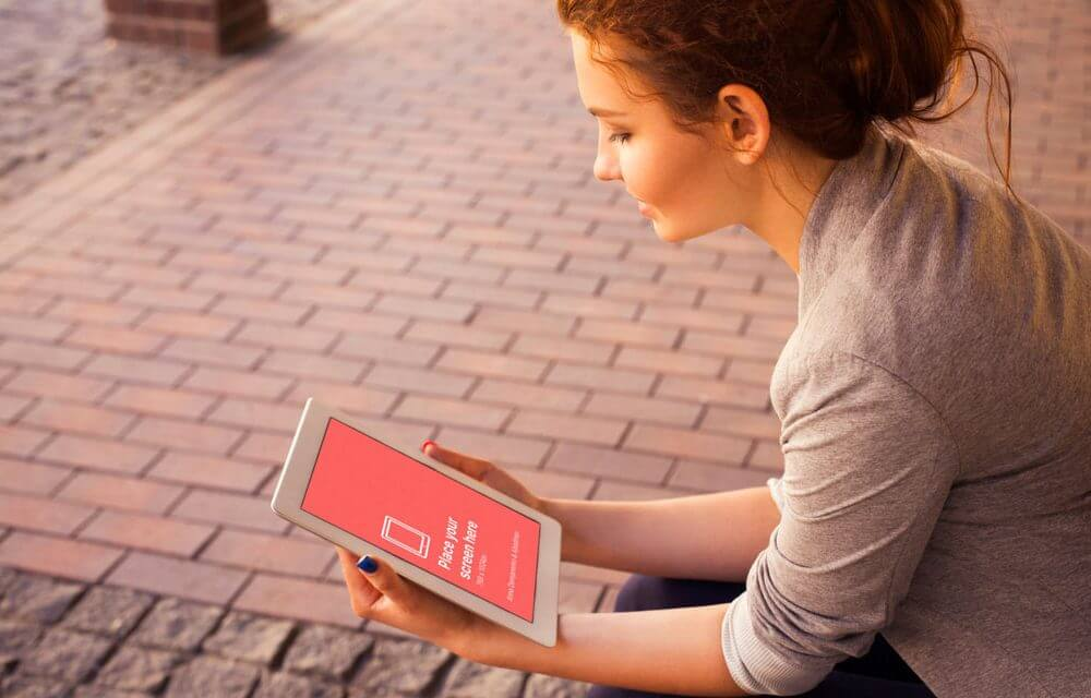 Young Woman looking at iPad Mockup
